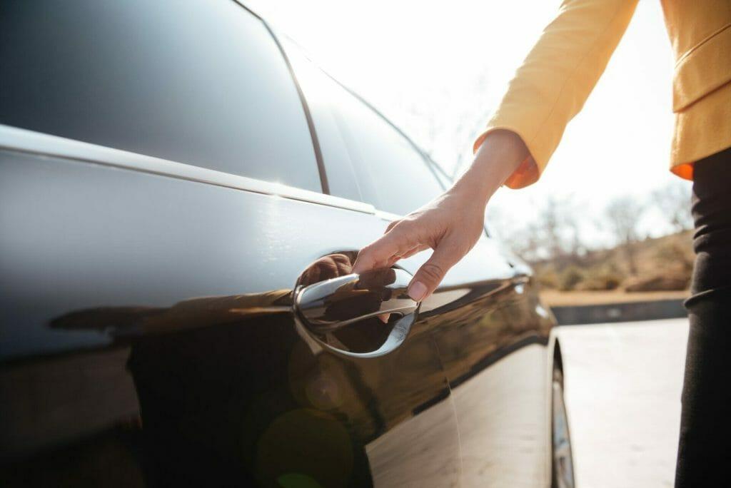 Businesswomen opening the door of black car